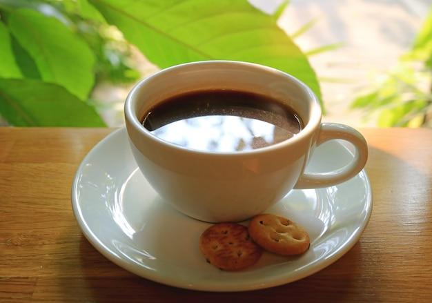 Xícara de café quente na mesa de madeira pela janela com folhas da árvore verde turva no fundo