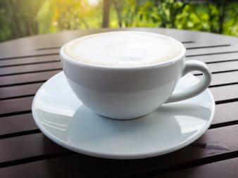 Xícara de café quente na mesa de madeira.