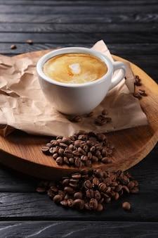Xícara de café quente na placa de madeira com grãos de café derramados