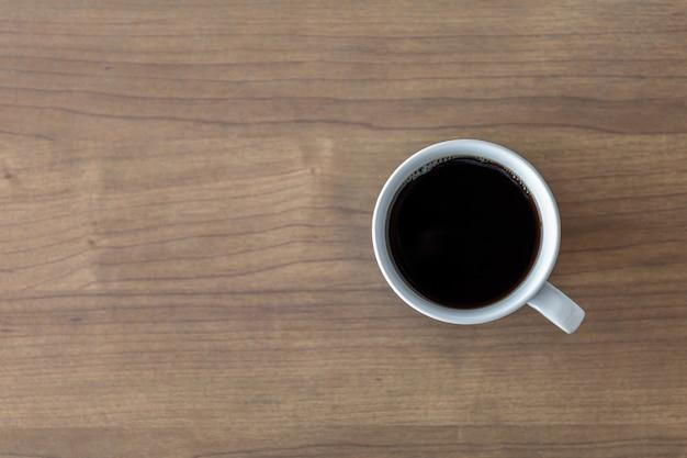 Xícara de café quente no fundo da mesa de madeira. vista do topo
