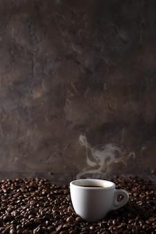 Xícara de café quente no fundo de grãos de café sobre um fundo escuro de madeira