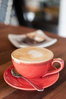 Xícara de café quente vermelho e padaria na mesa de madeira no restaurante