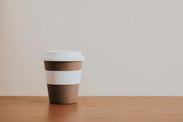 Xícara de café reutilizável de cortiça em mesa de madeira