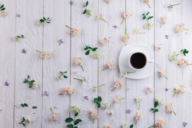 Xícara de café rodeada de flores em fundo branco