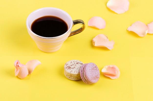 Xícara de café rosa com macarons coloridos e pétalas de rosa