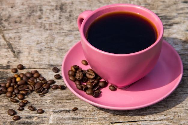 Xícara de café rosa e grãos de café na mesa de madeira rústica