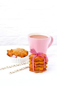 Xícara de café rosa e mesa de madeira branca de biscoito de gengibre