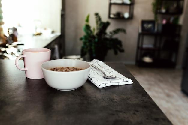 Xícara de café rosa, frutas picadas em uma tigela de mirtilos, colher na toalha na cozinha