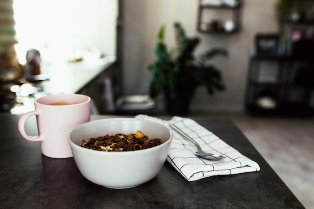 Xícara de café rosa, tigela com frutas tropicais picadas kiwi e banana, mirtilos, colher colher na toalha no balcão do bar na elegante cozinha loft.