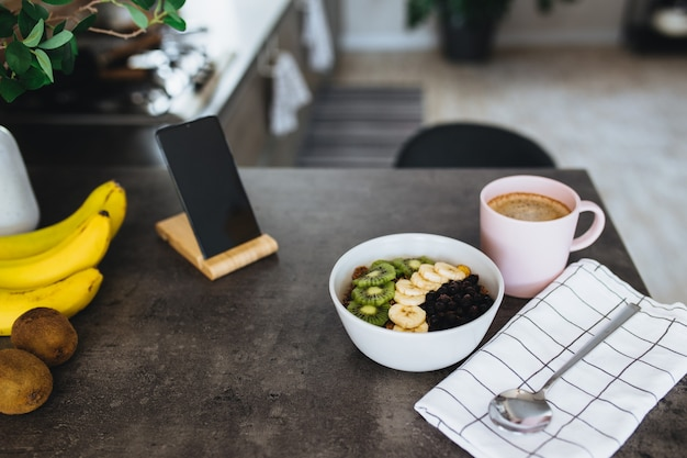 Xícara de café rosa, tigela com frutas tropicais picadas kiwi e banana, mirtilos, colher e celular no balcão do bar na cozinha elegante do sótão.