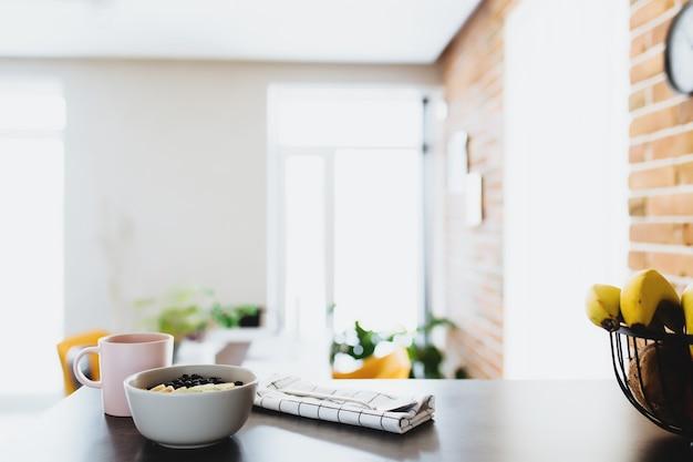 Xícara de café rosa, tigela com frutas tropicais picadas kiwi e banana, mirtilos, colher no balcão do bar na elegante cozinha loft.