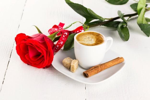 Xícara de café, rosa vermelha, açúcar e canela em um fundo branco de madeira