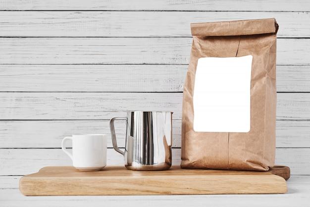 Xícara de café, saco de papel artesanal e jarra de aço inoxidável