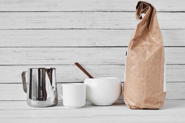 Xícara de café, saco de papel ofício e jarro inoxidável