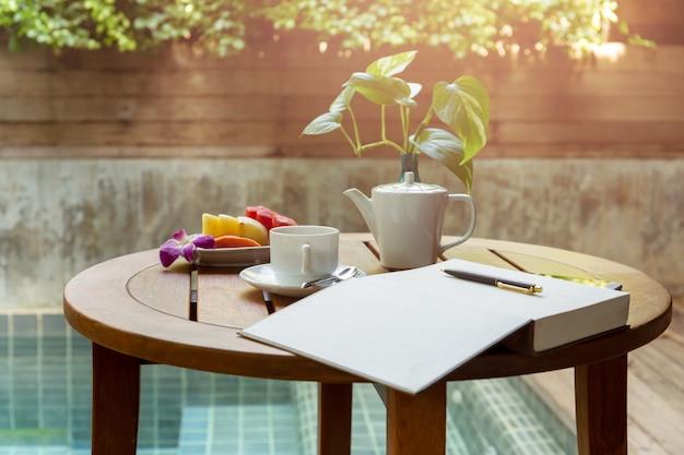 Xícara de café selecionada do foco e caderno aberto com a pena na tabela de madeira.