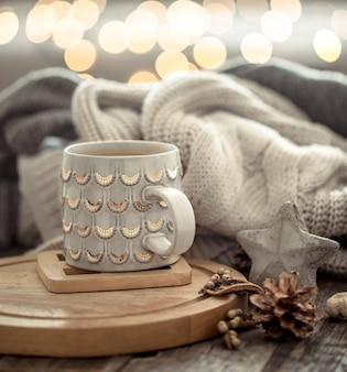 Xícara de café sobre bokeh de luzes de natal em casa na mesa de madeira com camisola na parede e decorações. decoração de férias