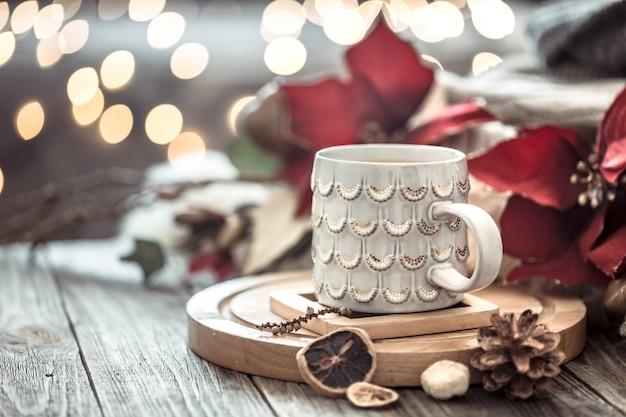Xícara de café sobre bokeh de luzes de natal em casa na mesa de madeira com flores na parede e decorações. decoração de férias, natal mágico