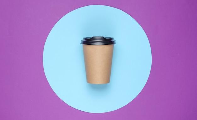 Xícara de café sobre fundo roxo com círculo azul pastel. vista do topo