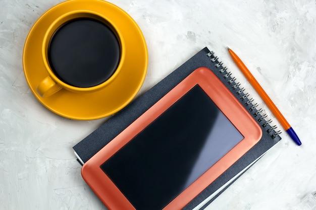 Xícara de café, tablet, caderno e caneta sobre uma mesa