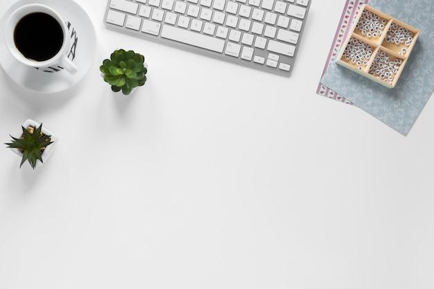 Xícara de café; teclado; planta de cacto e caixa com papéis de cartão no local de trabalho