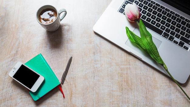 Xícara de café; tulipa no laptop; celular; caneta e livro na mesa de madeira