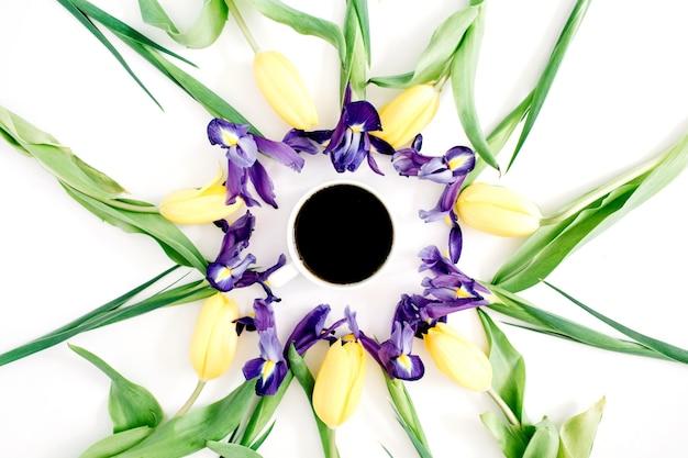 Xícara de café, tulipas amarelas e flores roxas de íris em branco