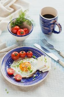 Xícara de café, um ovo, queijo e tomate cereja no café da manhã saudável.