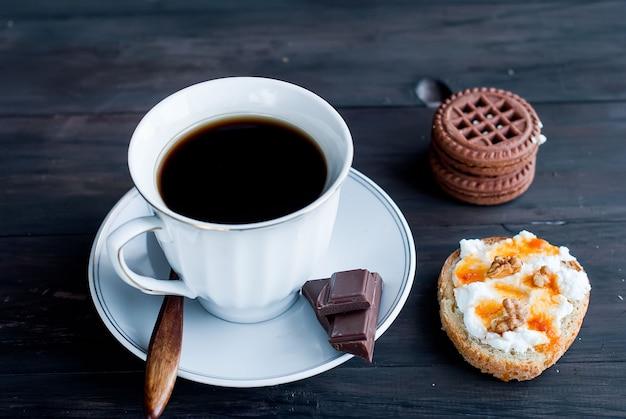Xícara de café, um sanduíche com ricota e biscoitos