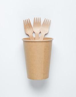 Xícara de café vazia descartáveis com garfos de materiais naturais em fundo branco. conceito ecológico.