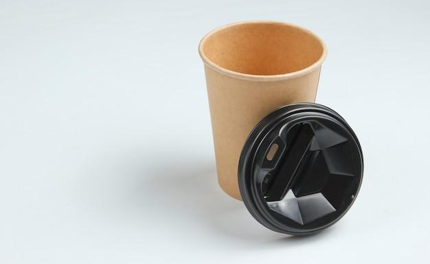 Xícara de café vazia descartável com materiais naturais em um fundo branco. conceito ecológico.