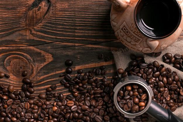 Xícara de café velha e turco com grãos torrados em uma mesa de madeira. conceito de aroma vintage em fundo escuro.