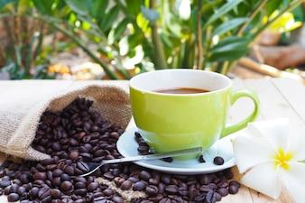 Xícara de café verde com saco de serapilheira de grãos de café na mesa de madeira