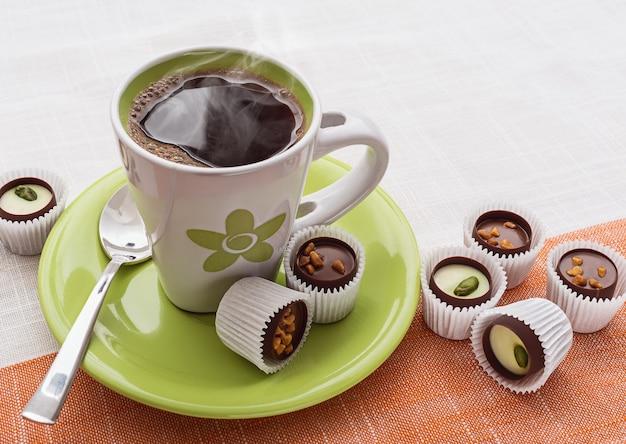 Xícara de café verde e chocolates