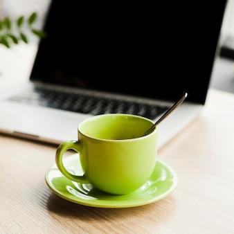 Xícara de café verde e laptop aberto na mesa de madeira