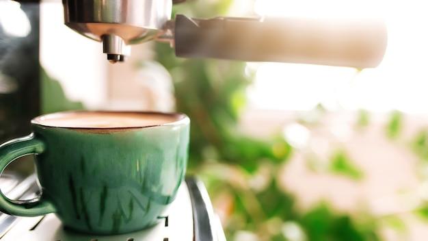 Xícara de café verde na máquina de café com dispensador. caneca cheia de café expresso, americano ou cappuccino. fundo desfocado. café da manhã na elegante cozinha, café ou restaurante.