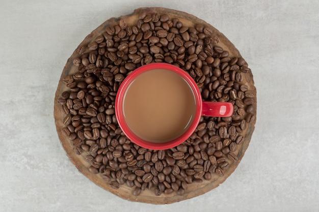 Xícara de café vermelha com grãos de café no pedaço de madeira