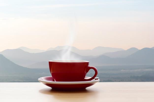 Xícara de café vermelha com manhã sol vista para a montanha