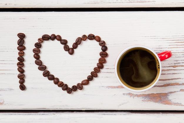 Xícara de café vermelha e feijão dispostos em forma de coração. eu amo café. madeira branca na superfície.