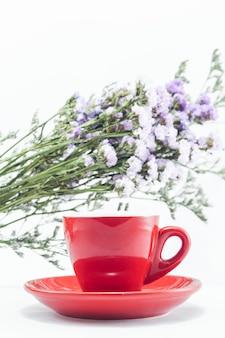Xícara de café vermelha e flor estática