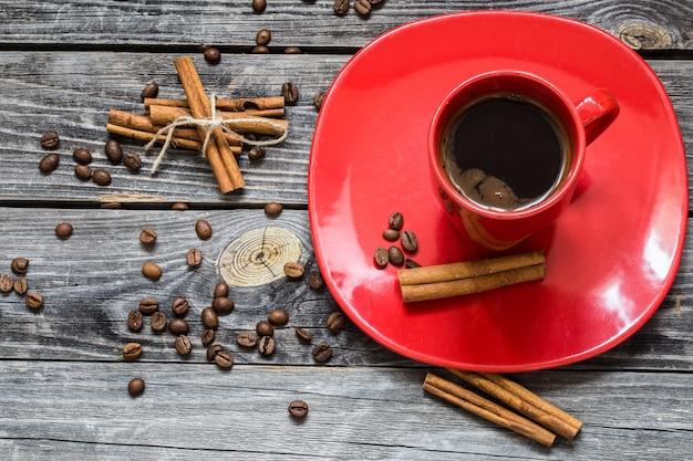 Xícara de café vermelha em um prato, parede de madeira, bebida