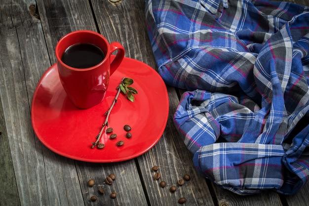 Xícara de café vermelha em um prato sobre um fundo de madeira bonito, bebida, grãos de café espalhados