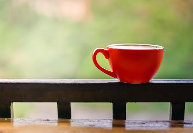 Xícara de café vermelha no trilho varanda de aço preto com fundo desfocado