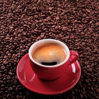 Xícara de café vermelho com café expresso e feijões roasted