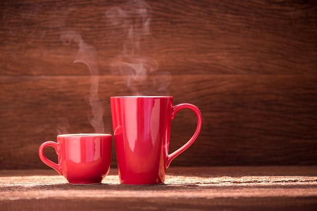 Xícara de café vermelho com fluxo de fumaça na mesa de madeira