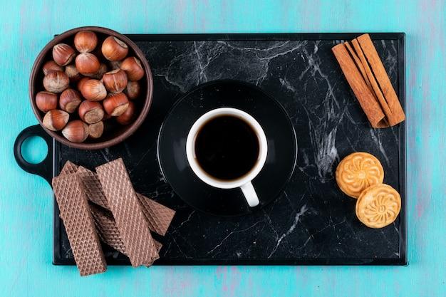 Xícara de café vista superior com biscoitos canela e nozes na bandeja preta