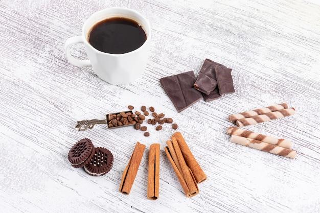 Xícara de café vista superior com biscoitos e canela na mesa branca