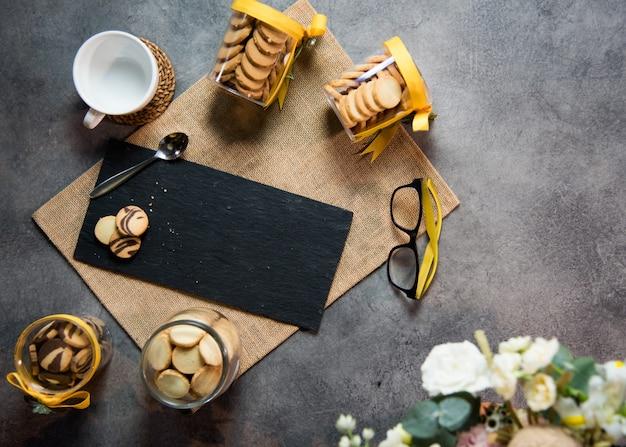 Xícara de café vista superior com biscoitos e superfície de mármore preto