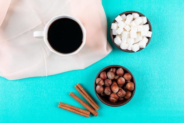 Xícara de café vista superior com cubos de açúcar canela e nozes na superfície verde