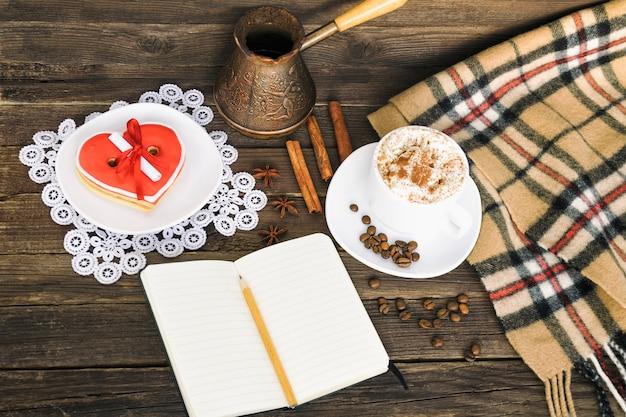 Xícara de cappuccino, biscoitos em forma de coração, mensagem de largura, caderno, lápis e cafeteiras na mesa de madeira marrom