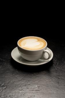 Xícara de cappuccino branca com um desenho de coração. uma xícara de café em uma mesa preta.